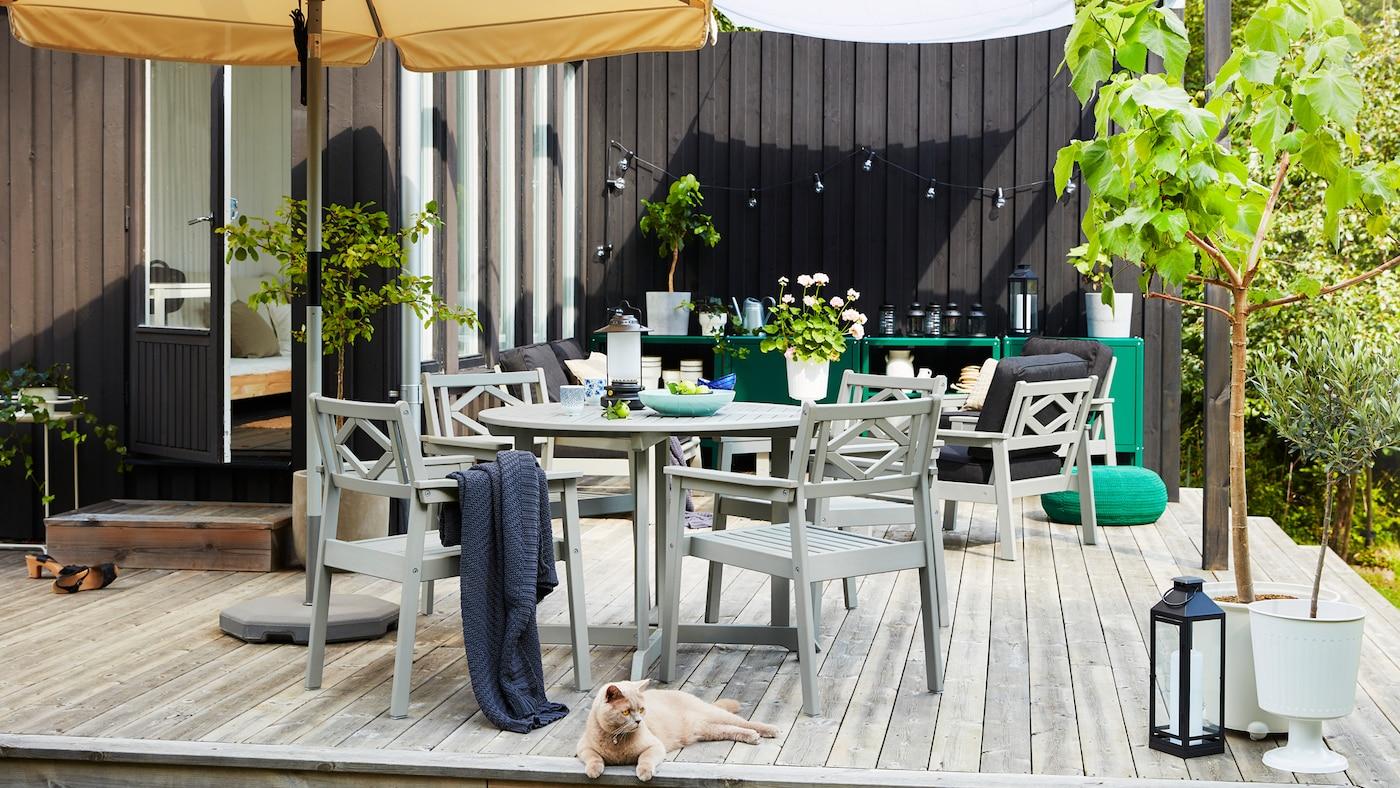 Een buitenruimte op een houten terras met een beige parasol, grijze buitenmeubels, groene bomen in een bloempot en een kat.