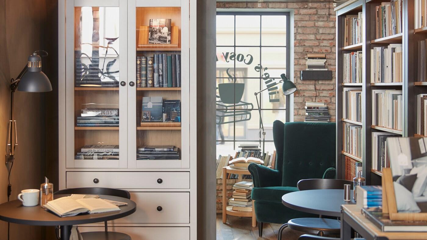 Een café met cafémeubels en grote boekenkasten, spots en een donkergroene fluwelen fauteuil.