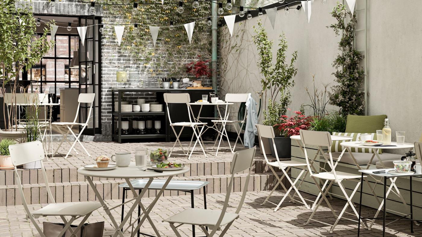 Een caféterras met beige stalen opklapbare tafels en stoelen, witte vlaggetjes, tegelvloeren en een serveerstation.