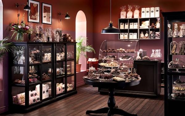 Een chocoladewinkel met een bruine kleur verf op de muur en IKEA MALSJÖ zwarte vitrinekasten met daarin verschillende verpakte chocolaatjes.