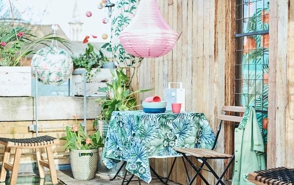 Een dakterras in de stad, met een terrastafel bedekt met stof met bladpatroon, klapstoelen, potplanten en gekleurde lantaarns.