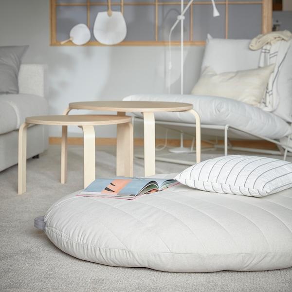 Een DIHULT poef met handgreep ligt op een vloerkleed in de woonkamer. Het is een ruim en comfortabel zitplekje voor kinderen.