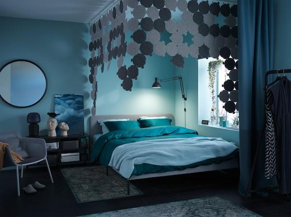 Een donkere, gezellige slaapkamer met groen en blauw beddengoed, geluiddempende panelen en vloerkleden.
