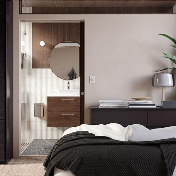 Een donkere mannelijke slaapkamer met een open deur en zicht op de badkamer