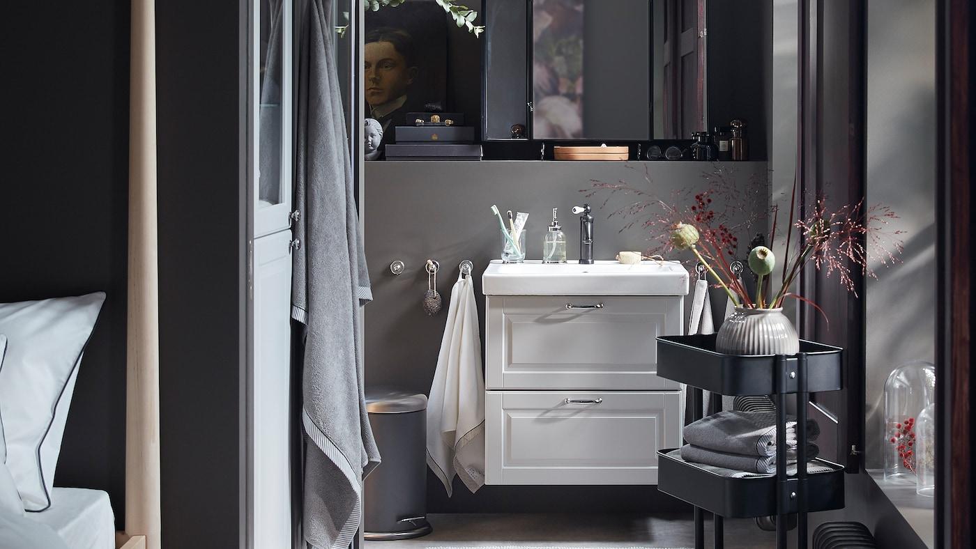 Een donkergrijze badkamer met een wastafel in lichtgrijs, een zwarte RÅSKOG trolley met opgevouwen handdoeken en decoratieve bloemen.