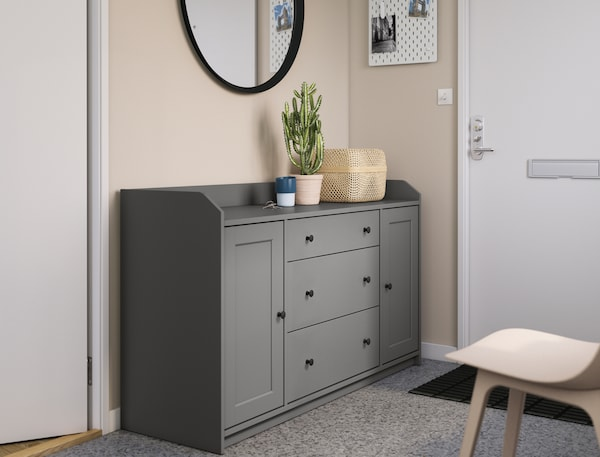 Een eenvoudig gemeubileerde hal met een spiegel, stoel en een grijze HAUGA buffetkast naast de voordeur.