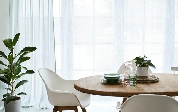 Een eetkamer met een ronde, houten tafel en witte stoelen, voor de hoge ramen met groene en witte gordijnen.