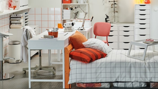 Een eigenzinnig kot met een wit bureau met een draaistoel aan een kant en een student die aan de andere kant zit.