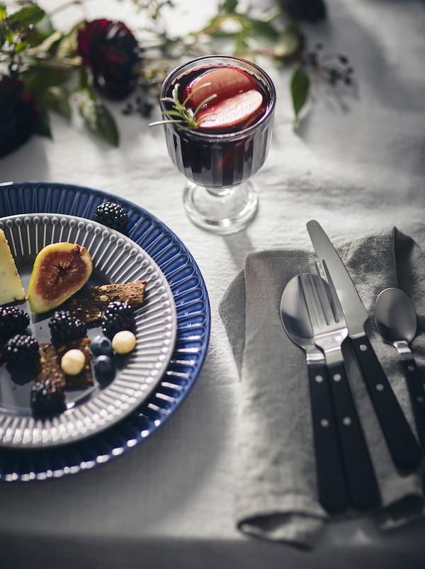 Een elegant gedekte tafel met een wit tafelkleed, een licht bord op een STRIMMIG bord en een drankje in een VARDAGEN glas.