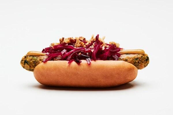 Een foto van de nieuwe IKEA veggie hotdog, geserveerd met ingelegde rode kool, knapperige gebakken uitjes en bruine mosterd.