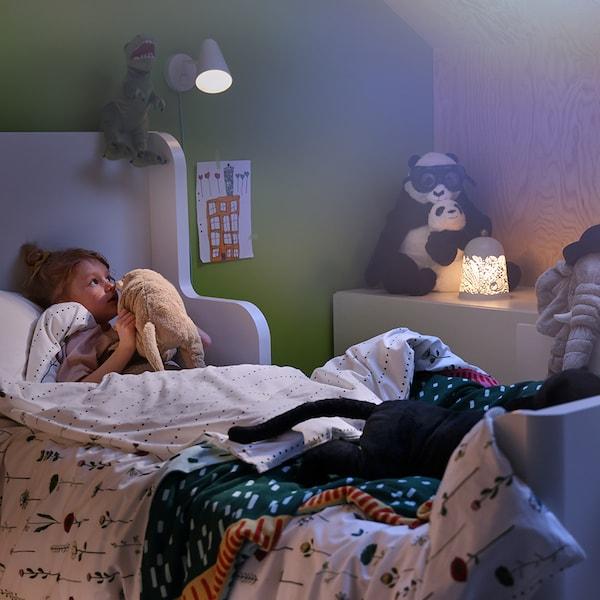 Een FUBBLA wandlamp en een SOLSKUR tafellamp verlichten een gezellige slaapkamer waar een meisje iets in het oor fluistert van haar favoriete knuffel.