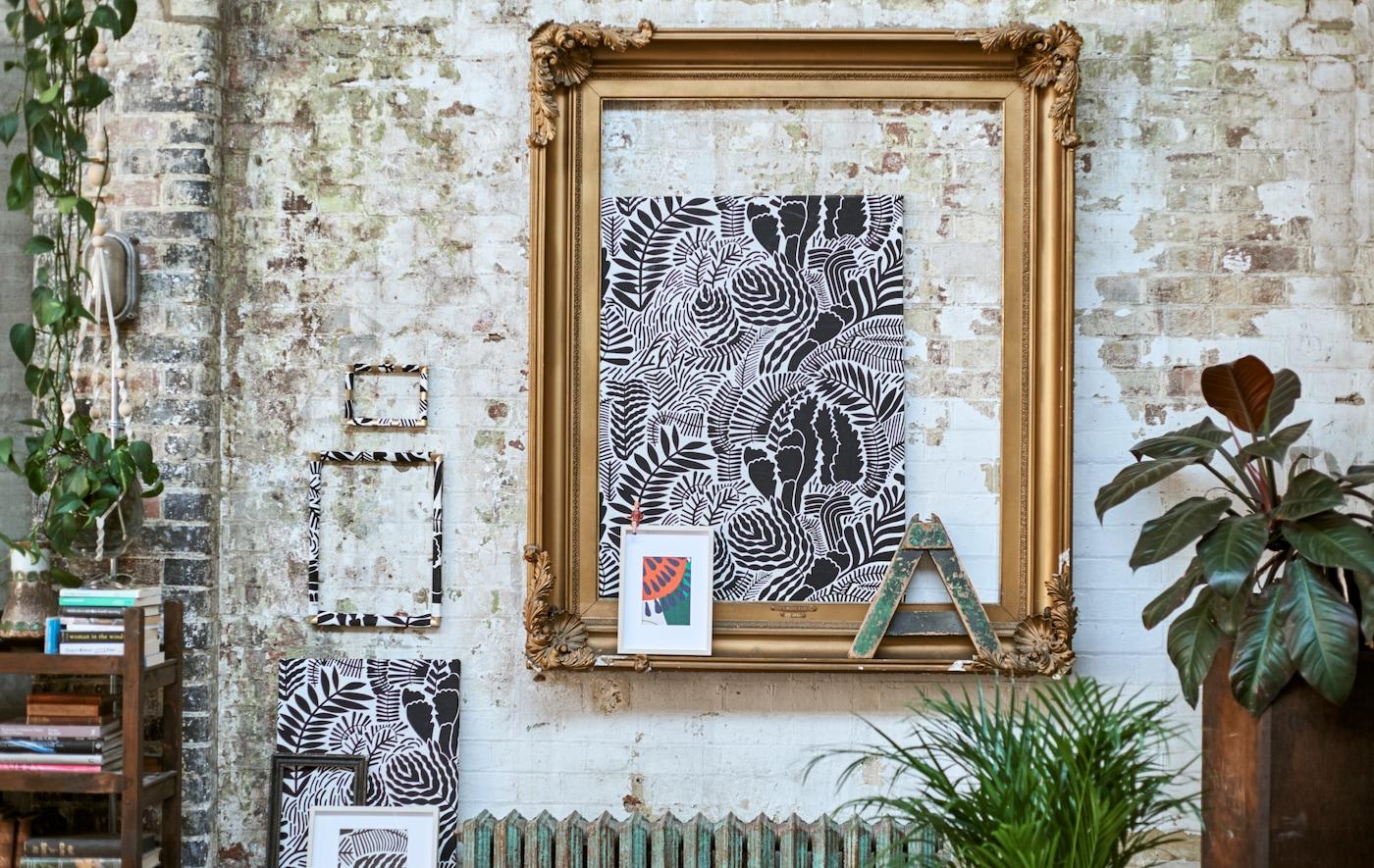 Een galerij van ingelijste, met patroon voorziene stoffen op een bakstenen muur met een grote gouden lijst, hangplanten en een lage boekenkast.