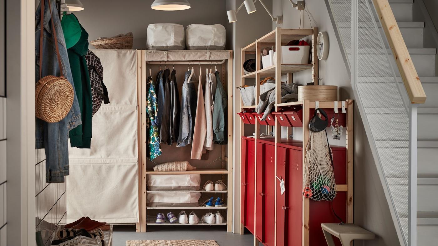 Een gang met IVAR rekken en opbergruimte, inclusief rode kasten en lades met kleding, schoenen en huishoudelijke spullen.