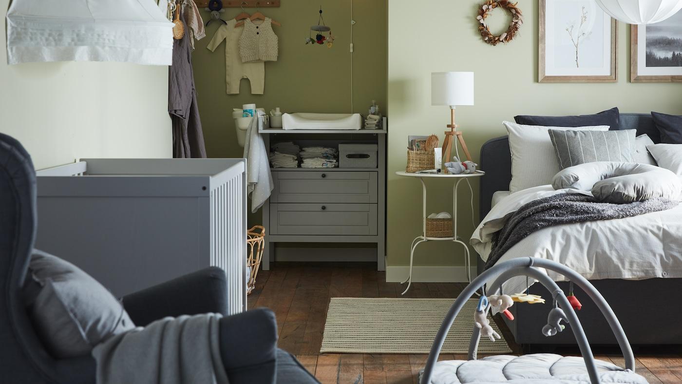 Een gecombineerde slaapkamer/babykamer met een grijs gestoffeerd bed, een grijs babybedje, een grijze commode met lades en groene wanden.