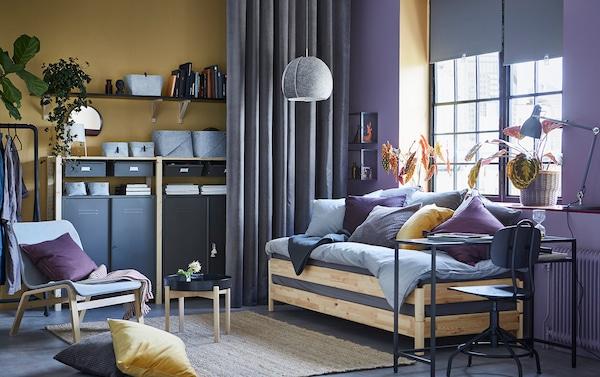 Een geel met paarse studio appartement met een praktisch houten UTÅKER bedbank, die gebruikt kan worden als bank, als een of twee losse bedden of als tweepersoonsbed. Het IVAR opbergsysteem in hout en metaal is zichtbaar op de achtergrond.