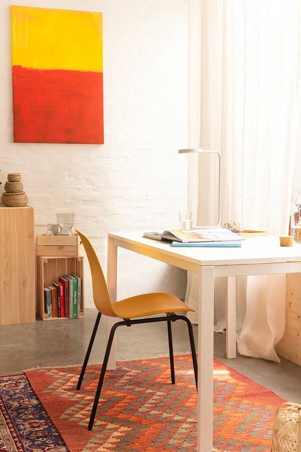 Een gele stoel aan een witte tafel die dienst doet als bureau op een oosters tapijt.