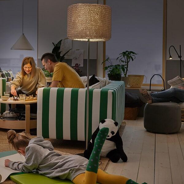 Een gezin dat samen thuis is. Een NÄVLINGE hanglamp, ISBRYTARE tafellamp en NÄVLINGE staande lamp verlichten de ruimte.