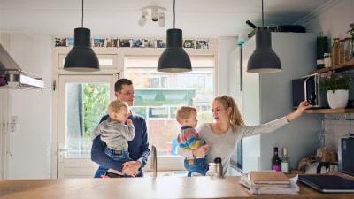 Een gezin in de keuken, vader en moeder, met elk een baby op de arm voor een venster en onder drie lampen.