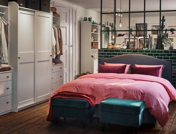 Een grijs HAUGA gestoffeerd tweepersoons bed in een slaapkamer waar langs een muur een grote witte HAUGA kastencombinatie staat.