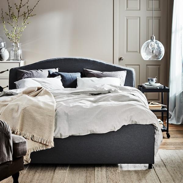 Een grijs HAUGA tweepersoonsbed met met wit bedtextiel in een lichte, zonnige slaapkamer. Een ladekastje staat achter het bed.