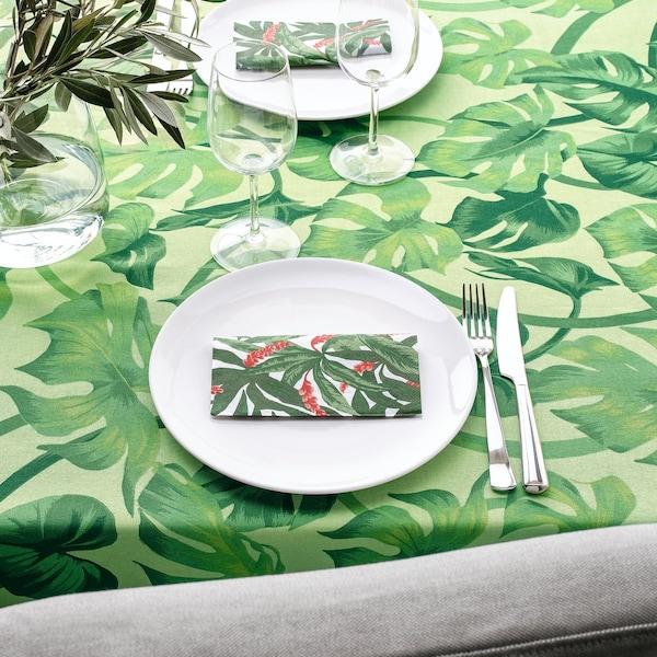 een groen tafelkleed met palmenpatroon gedekt met wit servies en tropische servetten