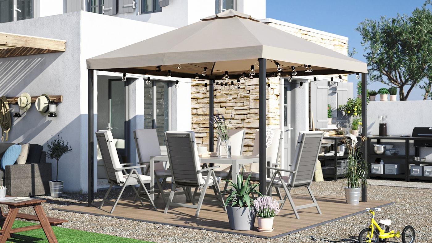 Een grote tuin met een eettafel, buitenstoelen met kussens, een partytent, vlonders met houtpatroon en een buitenkeuken.
