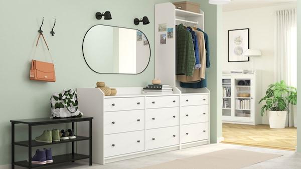 Een hal met een brede witte HAUGA kastencombinatie. In de kamer ernaast staat een wit HAUGA kastje met glazen deuren.