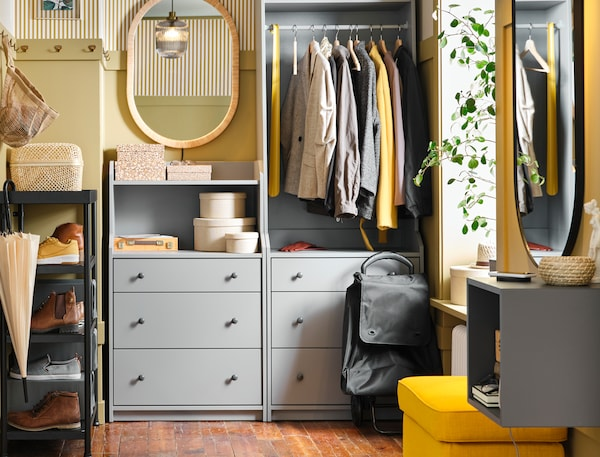Een hal met grijze HAUGA meubels, zoals een open garderobekast en een ladekast, met kleding en accessoires.