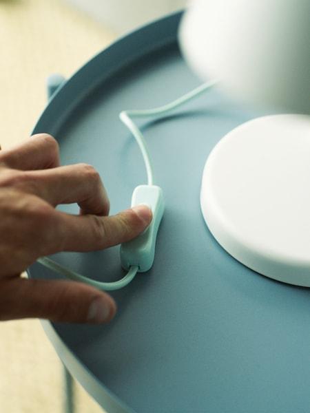 Een hand drukt op de schakelaar van een witte tafellamp die op een lichtblauwe tafel staat.