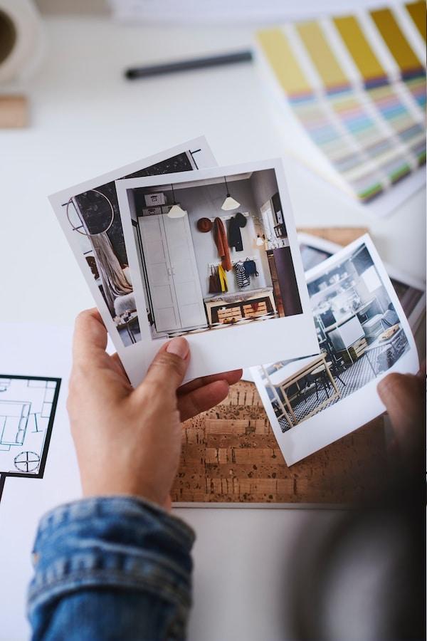 Een hand houdt een aantal inspirerende polaroids vast met beelden van interieurs op de achtergrond tekenmateriaal en een kleurenwaaier.