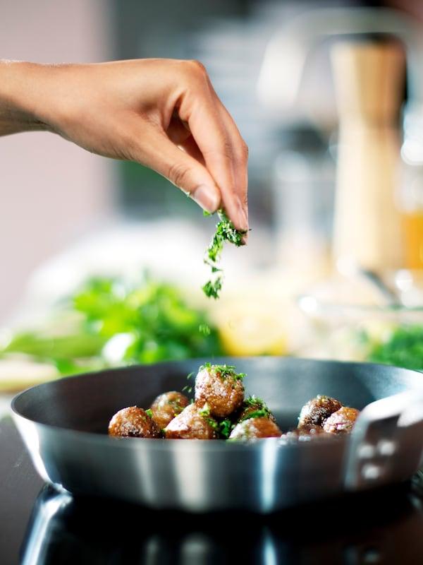 Een hand kruidt HUVUDROLL plantaardige balletjes in een IKEA 365+ koekenpan.
