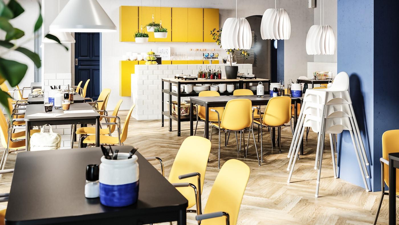 Een helder restaurant met donkergele stoelen, zwarte tafels, witte kinderstoelen, gele kasten en witte hanglampen.
