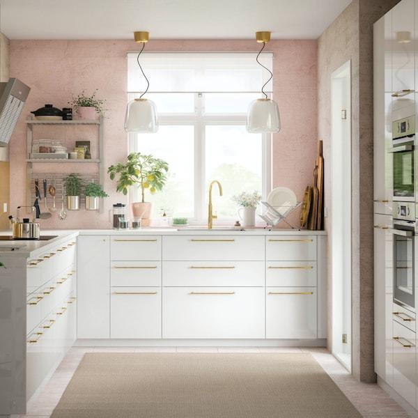 Een hoogglans witte RINGHULT keuken met gouden greepjes in een hoek