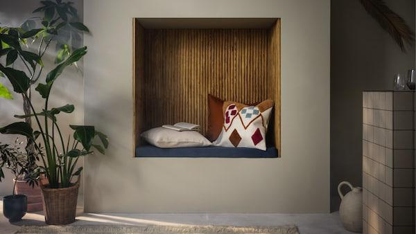 Een houten nis met gekleurde kussens om in te zitten in een witte muur.