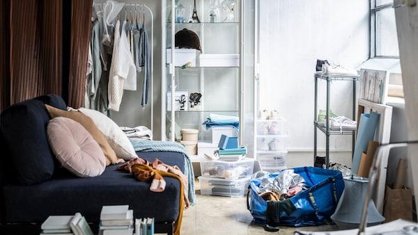 Een ietwat wanordelijke woonkamer met een blauwe zitbank, een schoenenrek, enkele stapelbare opbergdozen en een halfvolle FRAKTA tas.