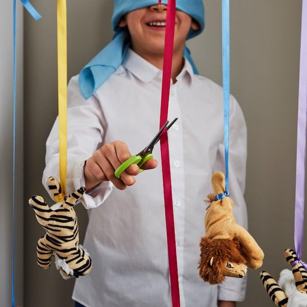 Een jongetje die geblinddoekt is speelt een spelletje waarbij hij lintjes moet doorknippen.