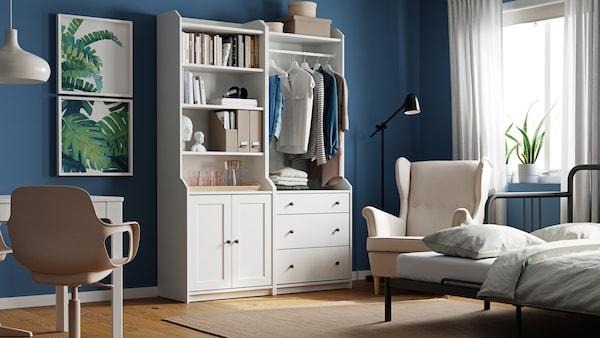 Een kamer met een witte HAUGA combinatie van hoge kasten, een bureau, een fauteuil en een bedbank in slaapstand.