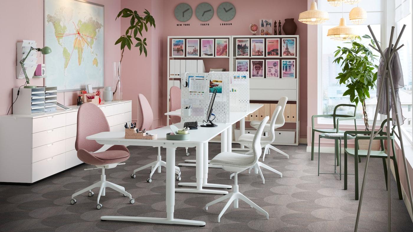 Een kantoorruimte met roze muren en witte BEKANT zit/sta-bureaus met HATTEFJÄLL draaistoelen.
