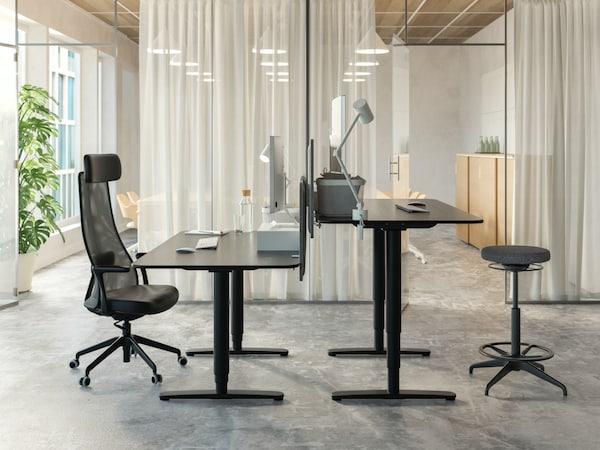 Een kantoorruimte met twee zwarte verstelbare bureautafels op een kale betonnen vloer, transparante gordijnen scheiden de bureaus van de rest ban deze grote ruimte