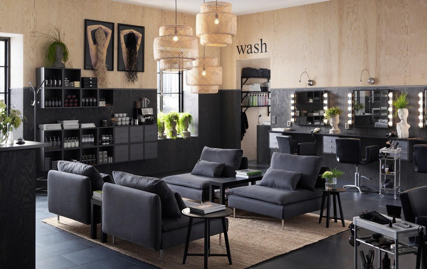 Een kapsalon gemeubileerd met de lage SÖDERHAMN donkergrijze fauteuils en wandkasten om haarproducten te presenteren.