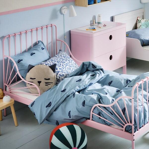 Een kinderkamer met een lichtroze MINNEN meegroeibed en een wit bed dat is opgedekt met blauw VÄNKRETS en BARNDRÖM beddengoed.