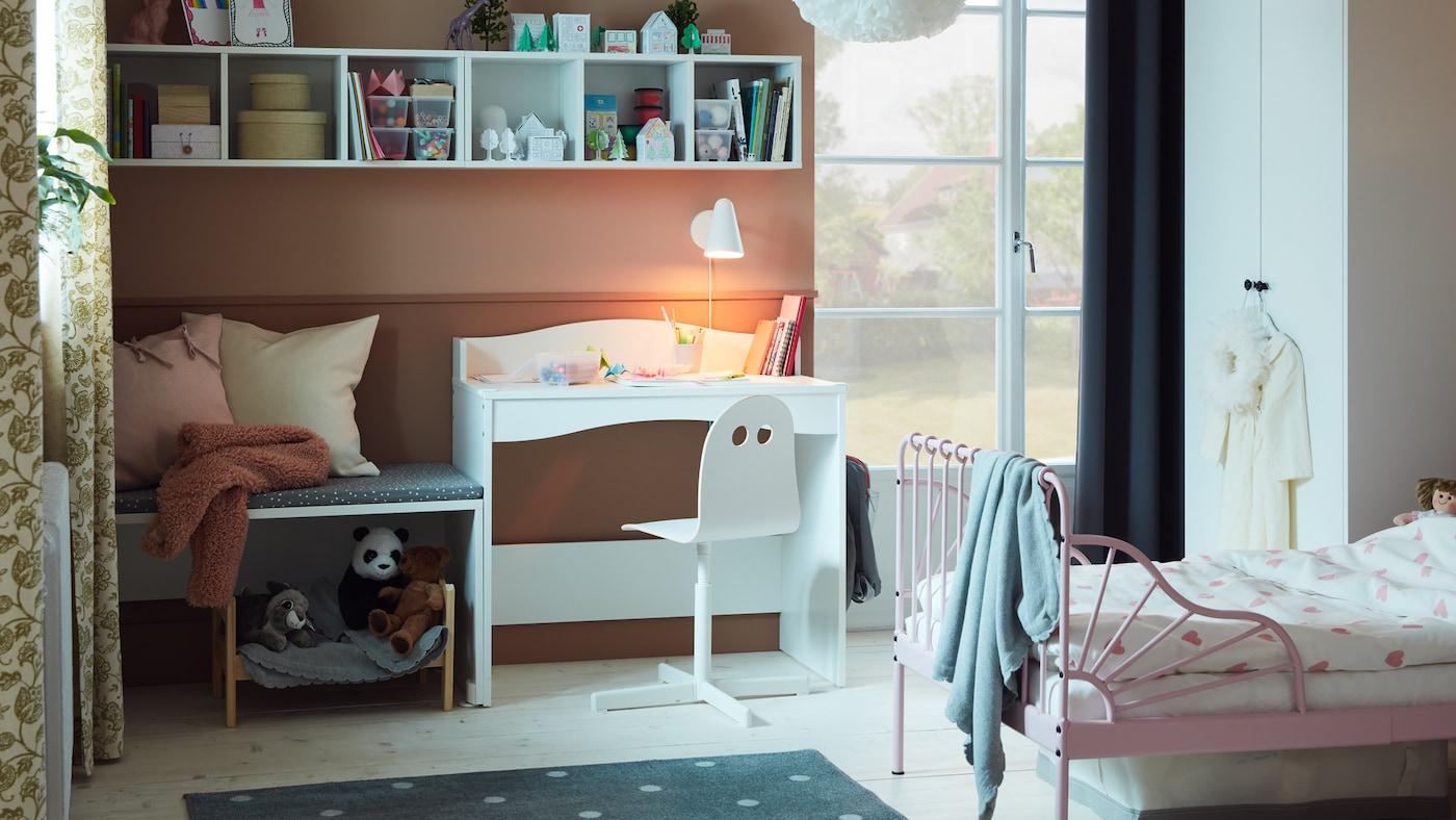 Een kinderkamer met een lichtroze uitschuifbaar bedframe met lattenbodem, wit bureau, boeken en zacht speelgoed.