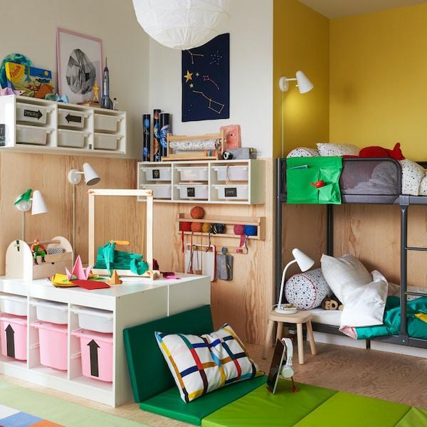 Een kinderkamer met een TUFFING stapelbed, TROFAST opberger en een zachte zitplek met een PLUFSIG opvouwbare gymnastiekmat.
