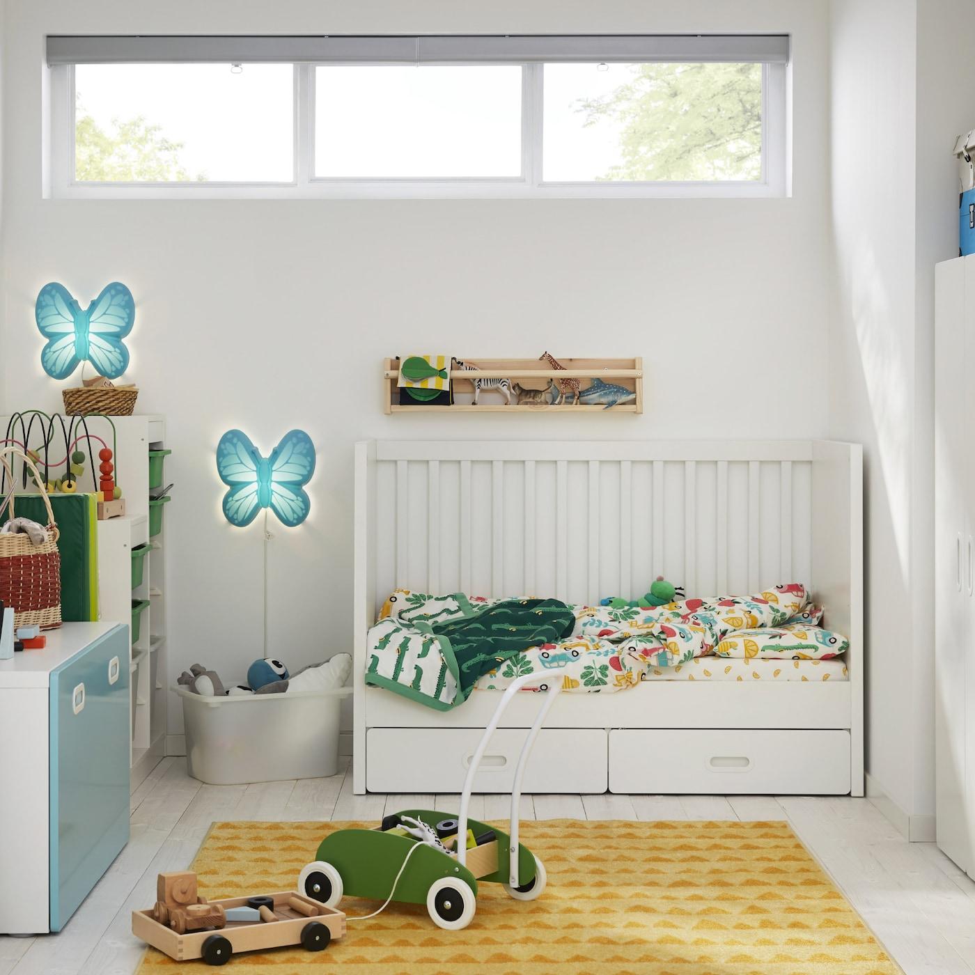 Een kinderkamer met een wit kinderbedje, een geel kleed, een witte kleerkast, een groene peutertruck en vlindervormige wandlampen.