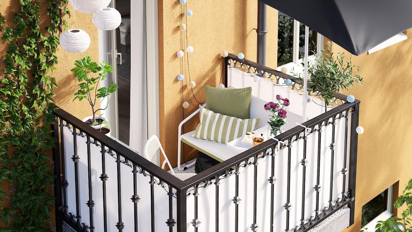 Een klein balkon van een geel flatgebouw, een witte bank, lichtkettingen en een tafeltje aan de reling.