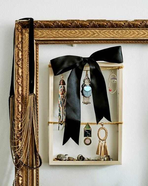 Een klein houten frame wordt gebruikt om hangende oorringen en een zwarte strik te tonen en hangt in een groot verguld frame.