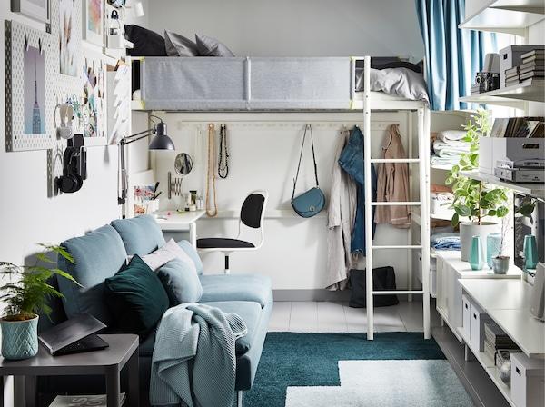 Een kleine studio/eenkamerappartement in grijs, groen en wit met een hoogslaper met daaronder een bureau.