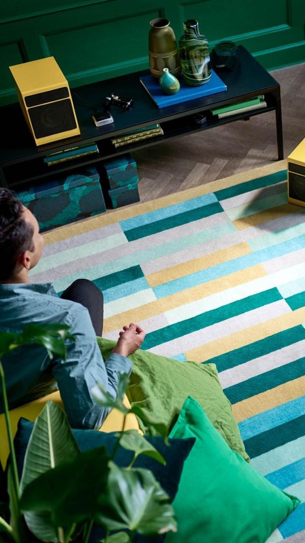 Een kleurrijk vloerkleed en de onderkant van een trap met een houten leuning, een groene plant, blauwe muren en een deurgat.