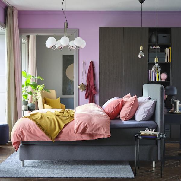 Een kleurrijke slaapkamer met lila muren, roze beddengoed, een gele sprei, een zwartbruine kast en een grijs bed.