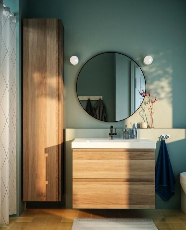 Een kolomkast en een houtkleurige onderkast voor een witte vierkante lavabo onder een grote ronde spiegel met zwarte rand tegen een groene muur.
